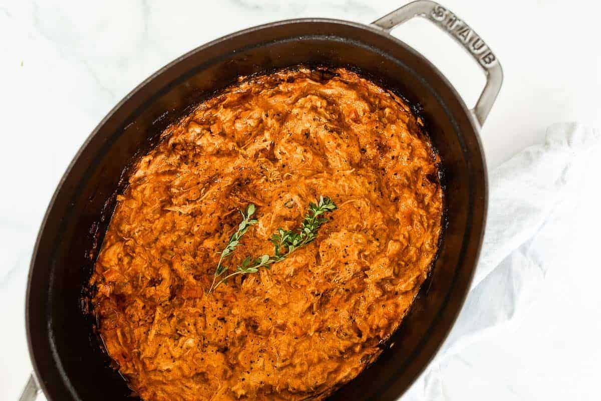An oval cast iron coquette filled with a pork ragu recipe.