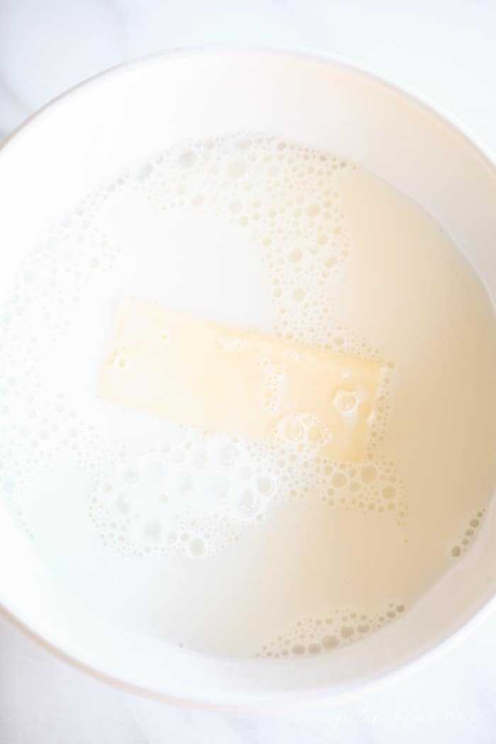 A bowl of milk with a stick of butter inside for an easy dinner roll recipe.