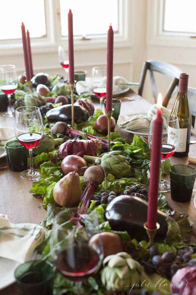 A fruit and vegetable fall centerpiece with taper candles on a long farm table.