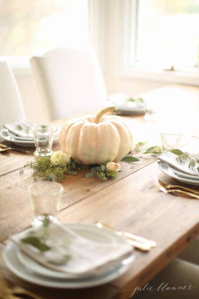 A wooden farm table set for a fall party with a white pumpkin and fresh flowers as a fall centerpiece.