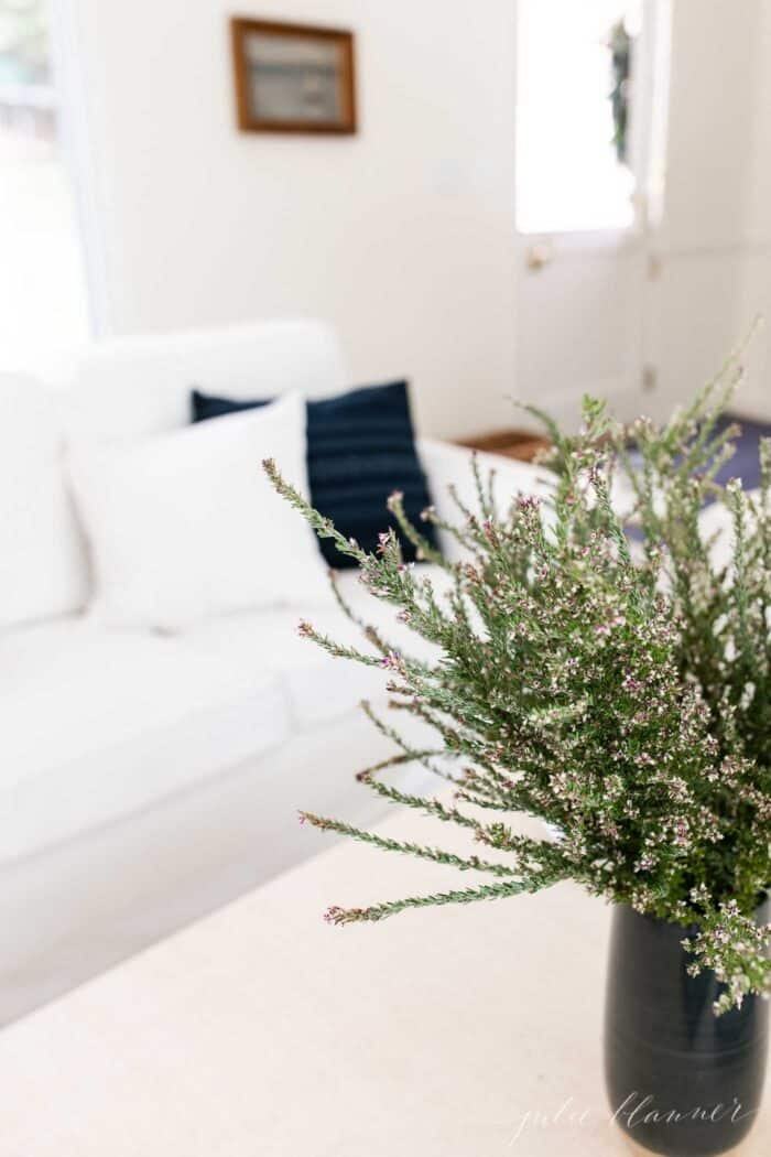 A white living room with navy pillows and a navy vase full of fall wildflowers.