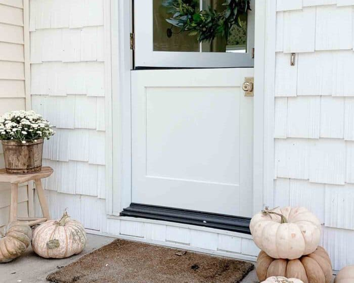 fall porch decor with wreath on dutch door pumpkins and mums