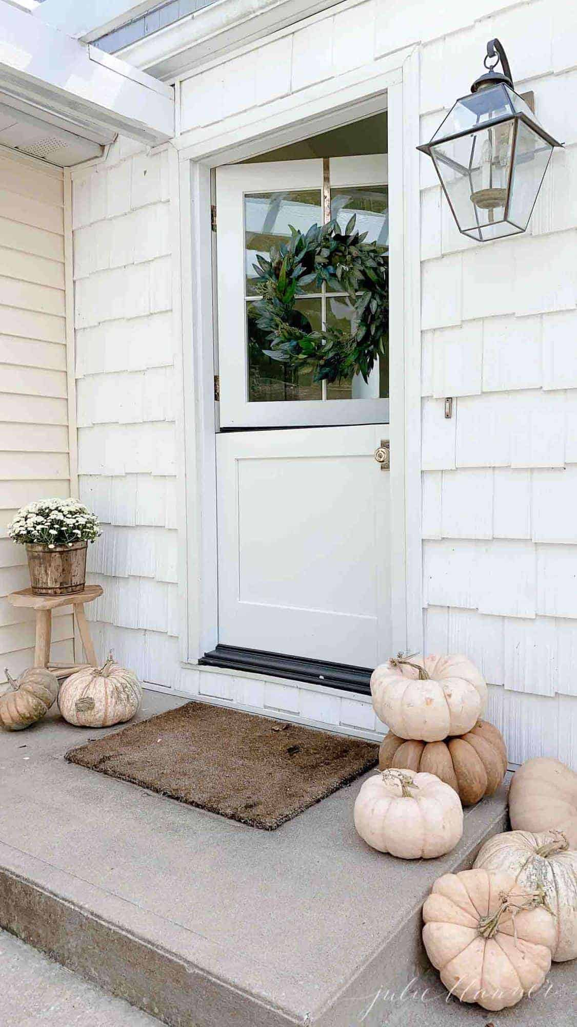 white house with dutch door fall wreath mums and pumpkins stacked