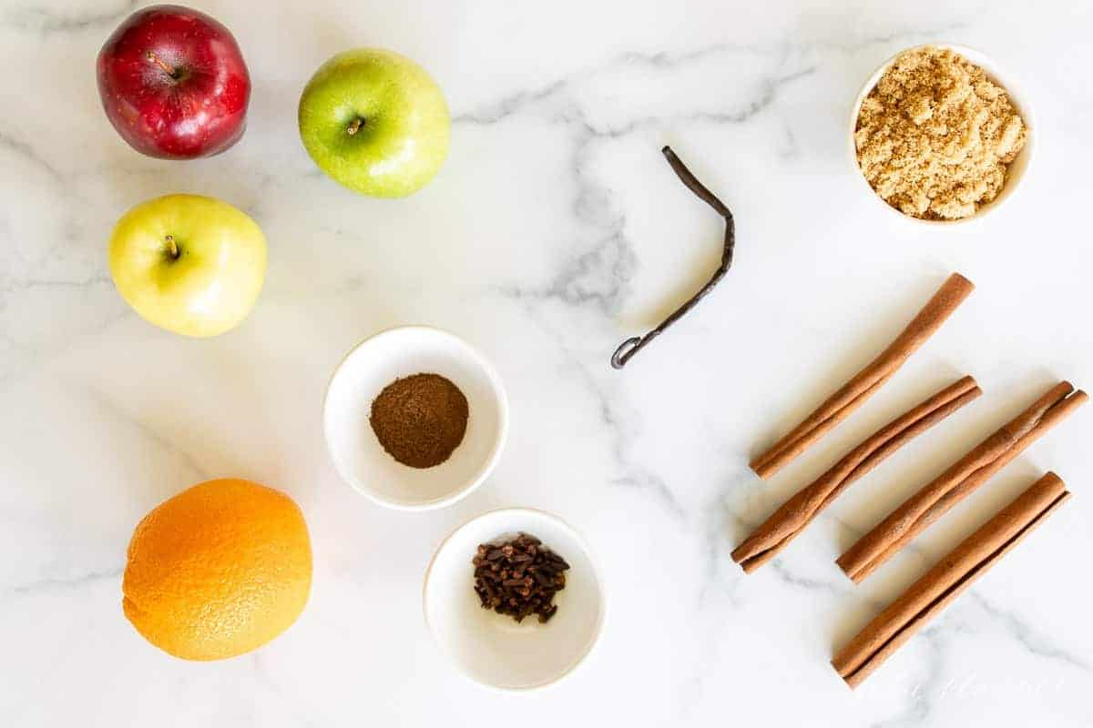 A marble surface with the ingredients for a homemade cider recipe laid out.