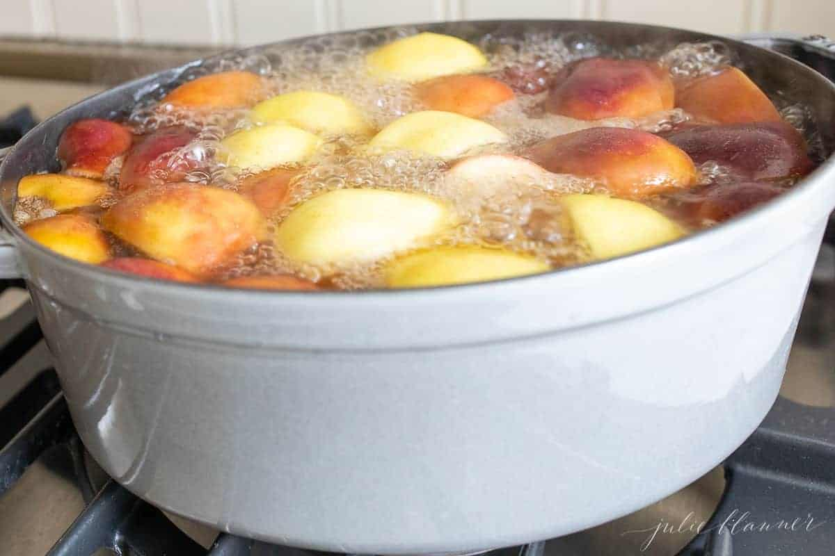 A cast iron pot filled with orange slices , apple slices and more to make a homemade apple cider recipe.