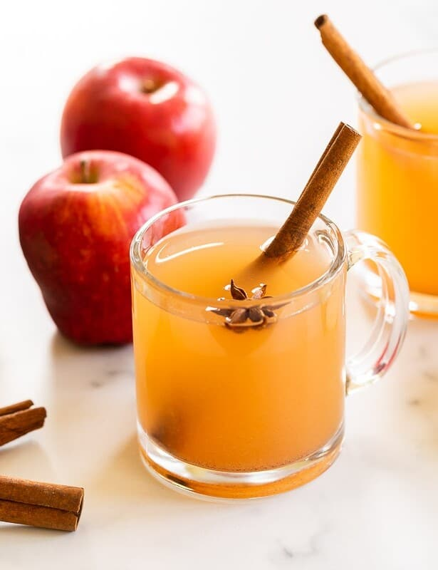 A marble surface with clear mugs full of homemade apple cider, whole apples and cinnamon sticks to the side.