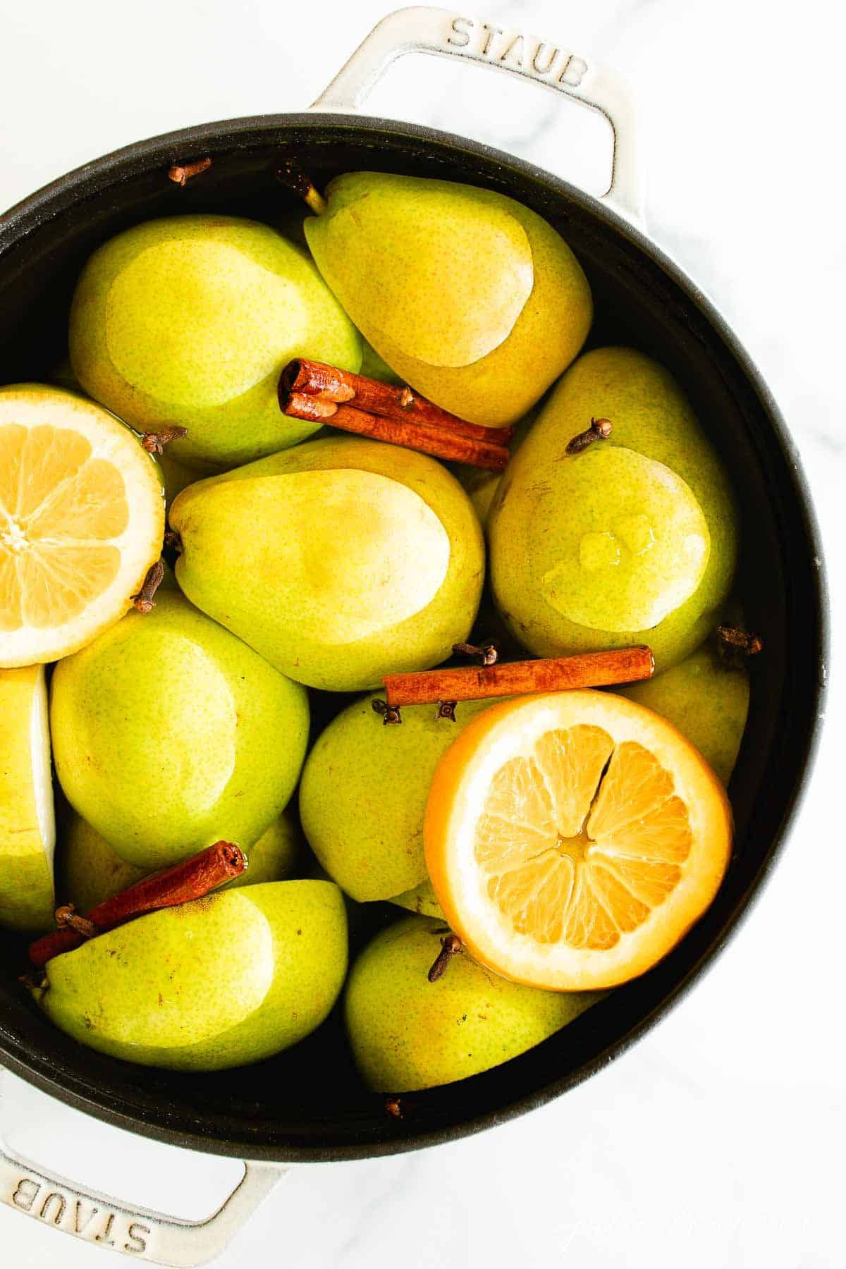 A cast iron pot filled with pear cider recipe ingredients