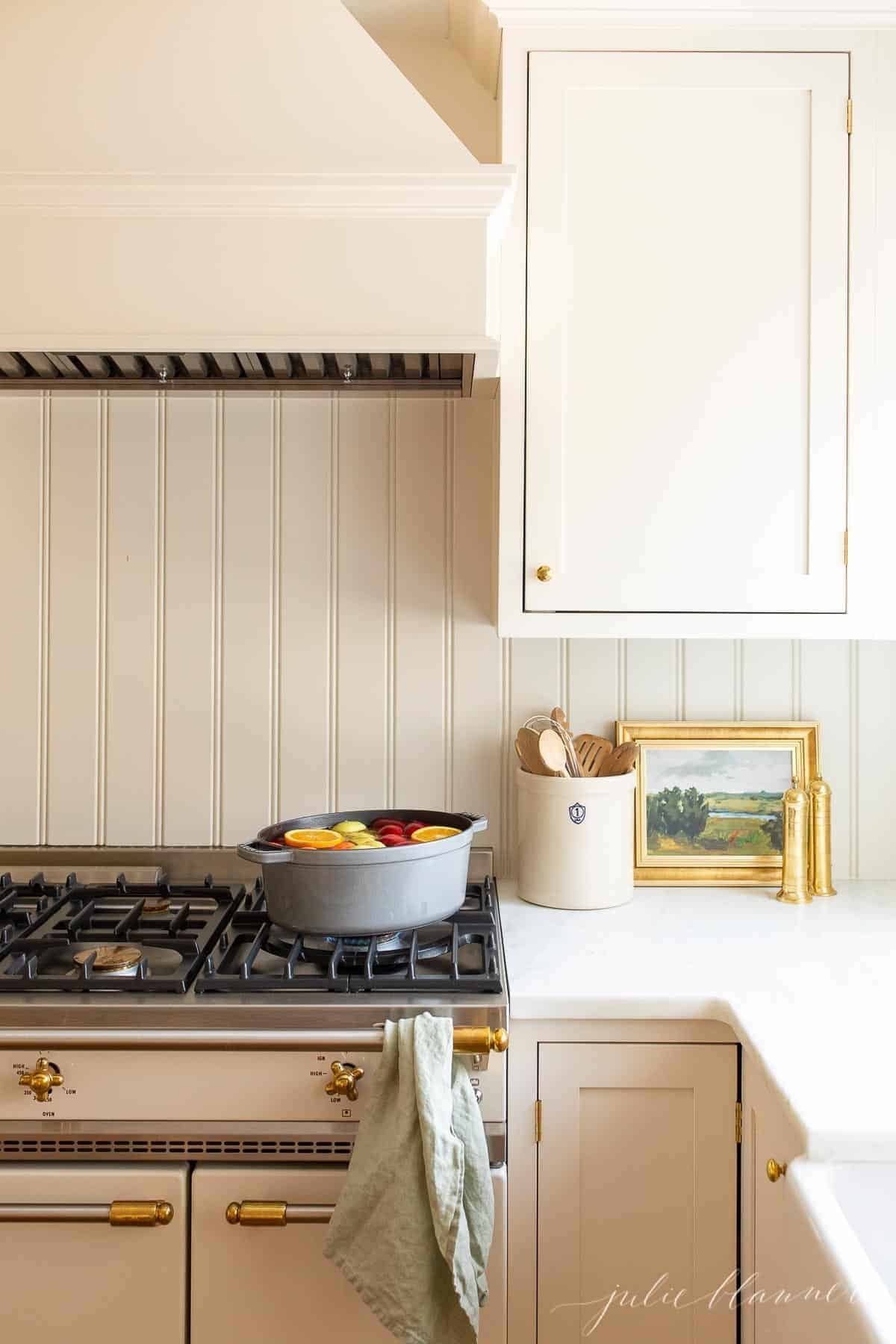 Two cast iron pots on a stove in a white kitchen filled with a homemade apple cider recipe simmering.