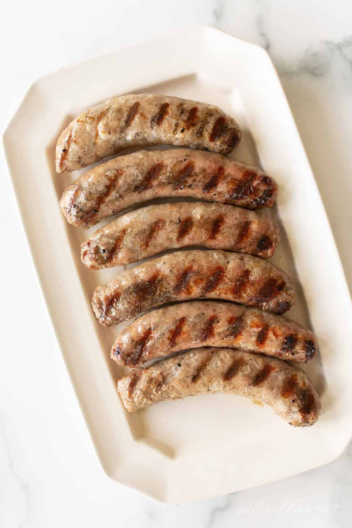 A white rectangular tray filled with cooke bratwurst sausages.
