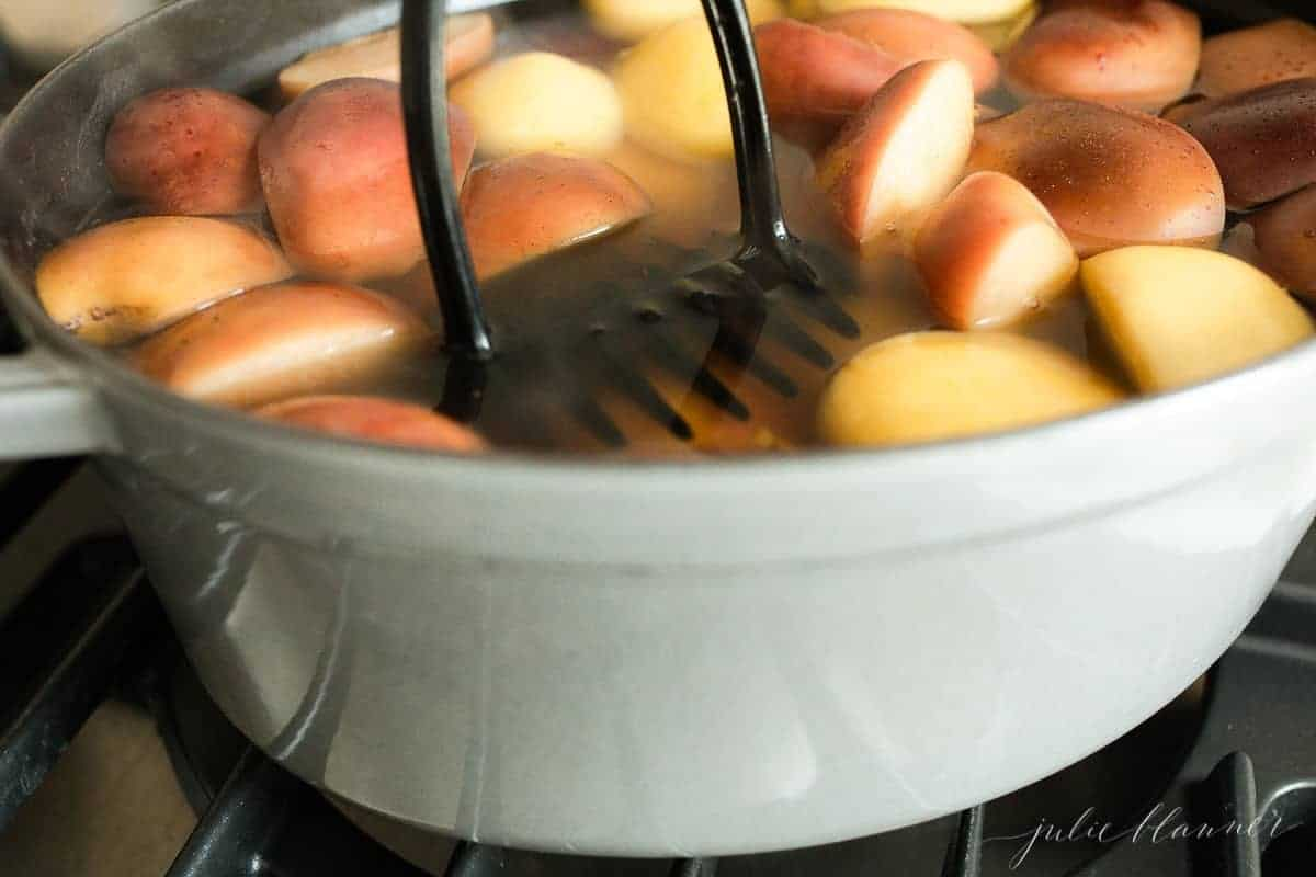 Close up shot of sliced apples in a pot of water, boiling into a homemade apple cider recipe, a potato masher in the pot.