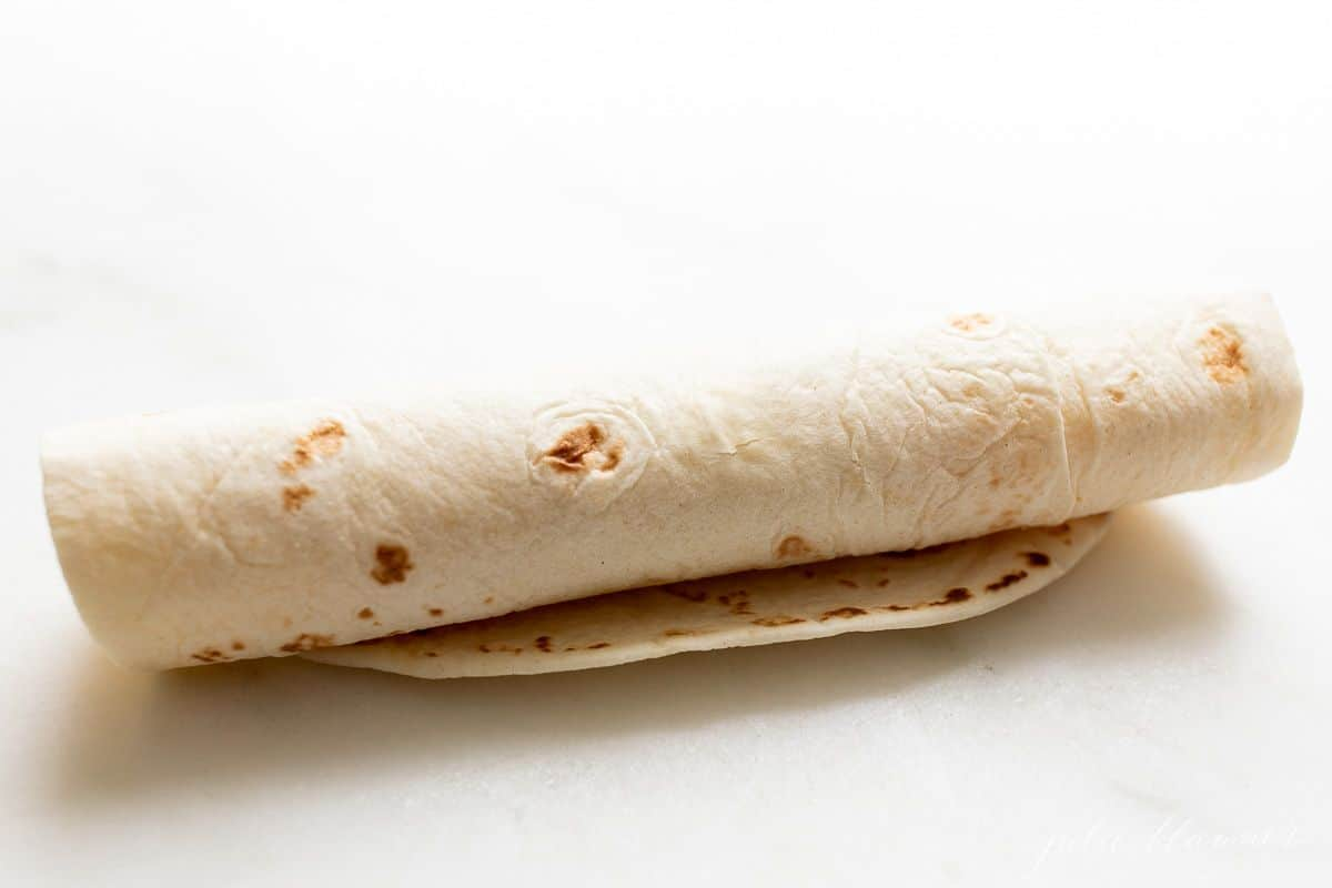 A flour tortilla rolled up on a marble surface.
