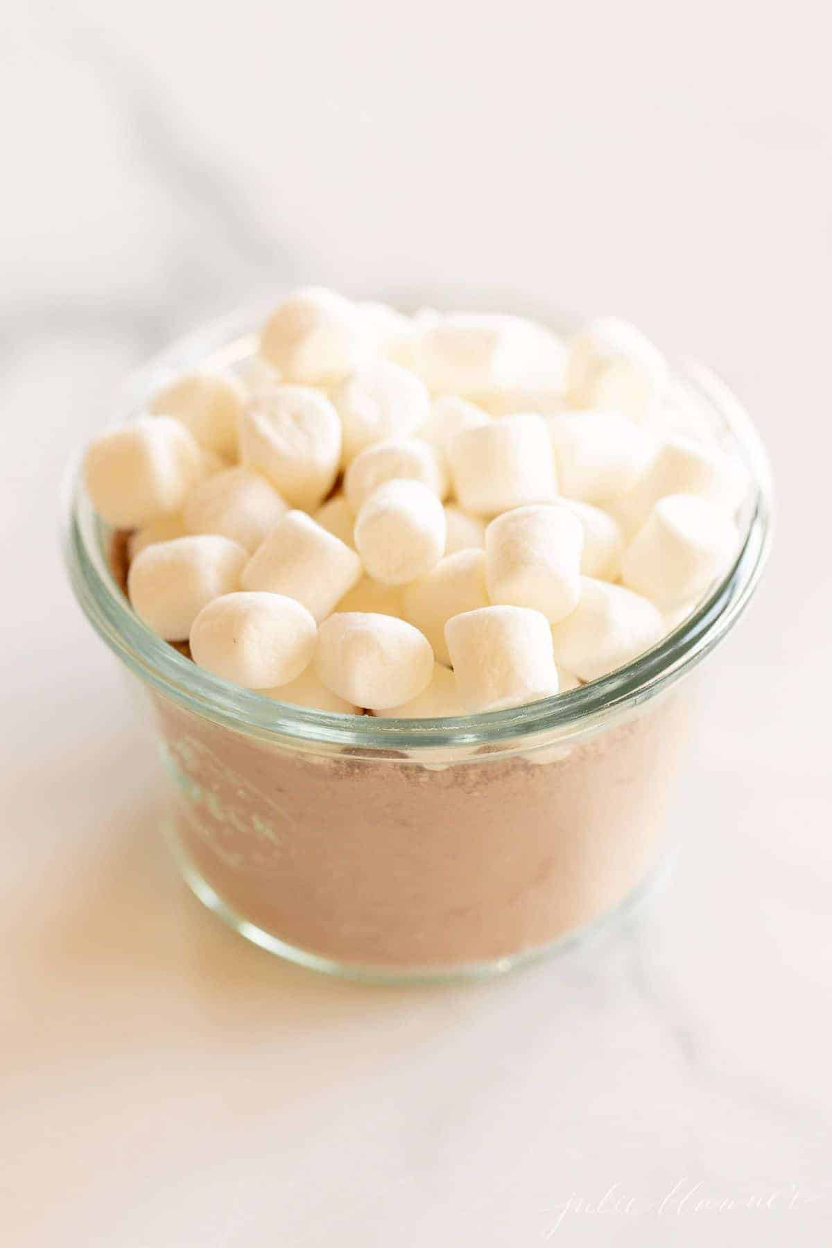A small glass jar full of homemade hot chocolate mix topped with small marshmallows.