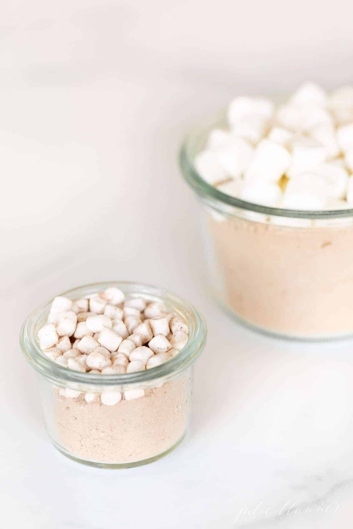 Two glass jars full of homemade hot chocolate mix topped with small marshmallows.