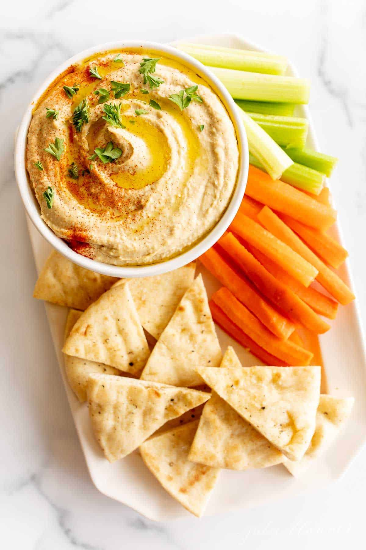 A bowl full of homemade hummus sitting on a platter of vegetables for dipping.