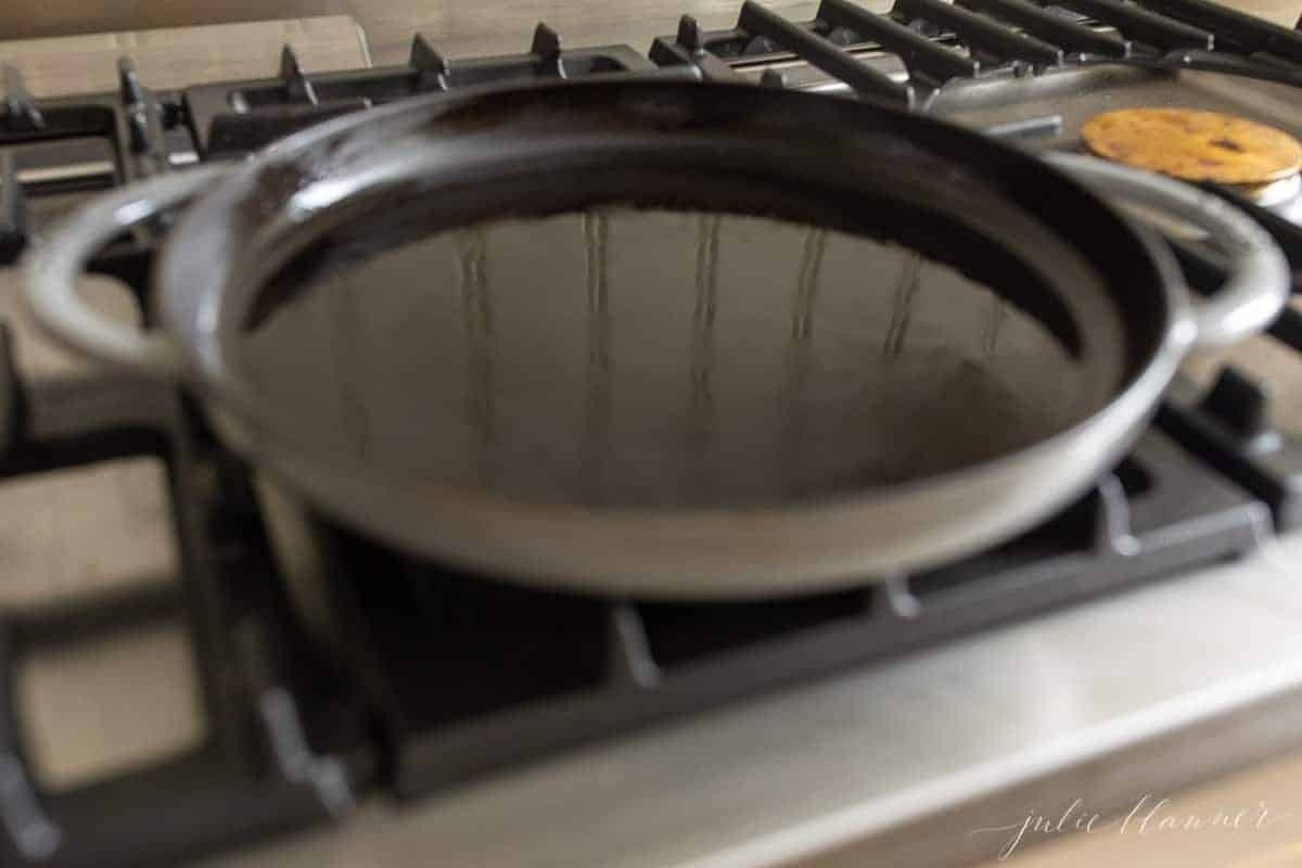 A cast iron pan on a stove top with a little olive oil heating inside.