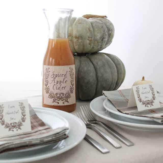 jar filled with apple cider with printed fabric label on table setting, pumpkins stacked in the background.