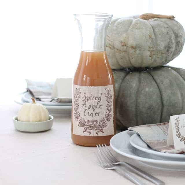 jar filled with apple cider with printed label on table setting, pumpkins stacked in the background.
