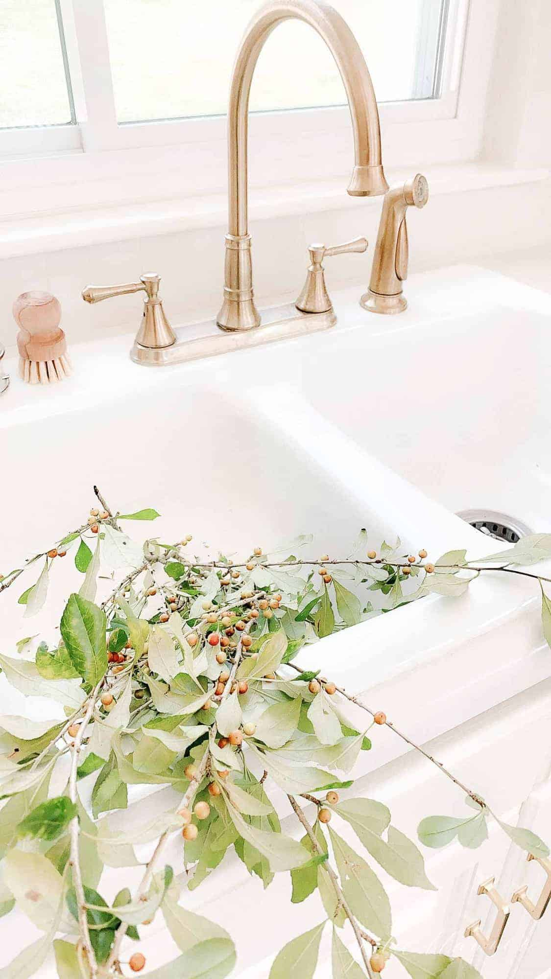 sink with brass faucet filled with fall branches