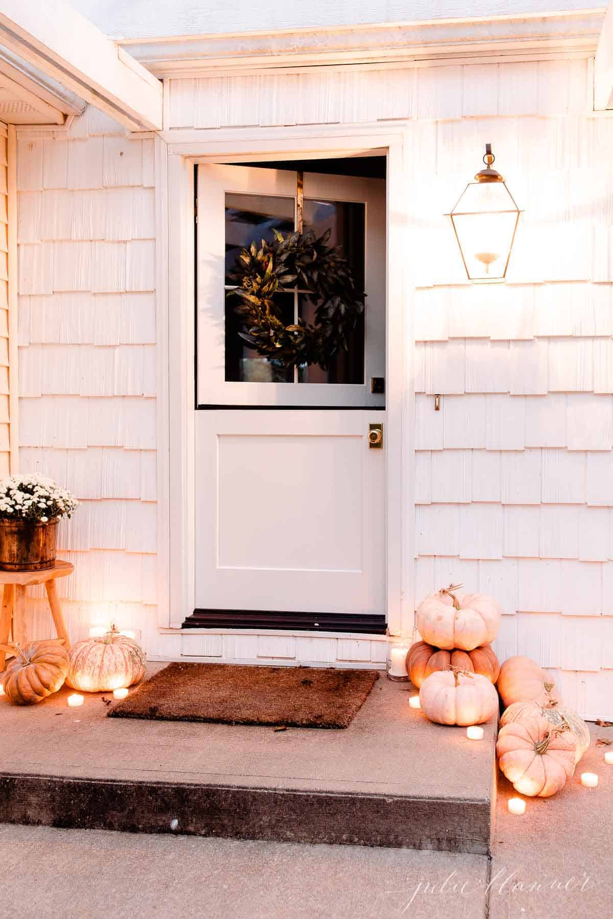 front door with pumpkins mums and candle light