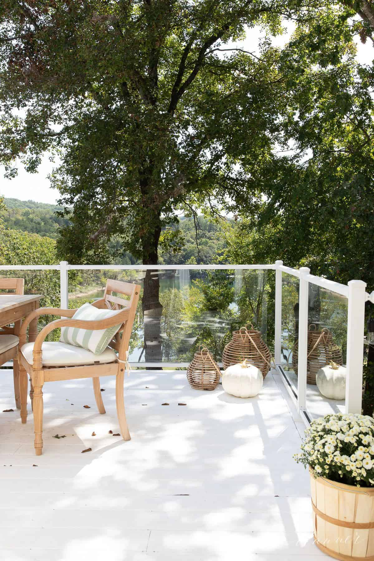 A white deck decorated with glass railings and white moms and white pumpkins.