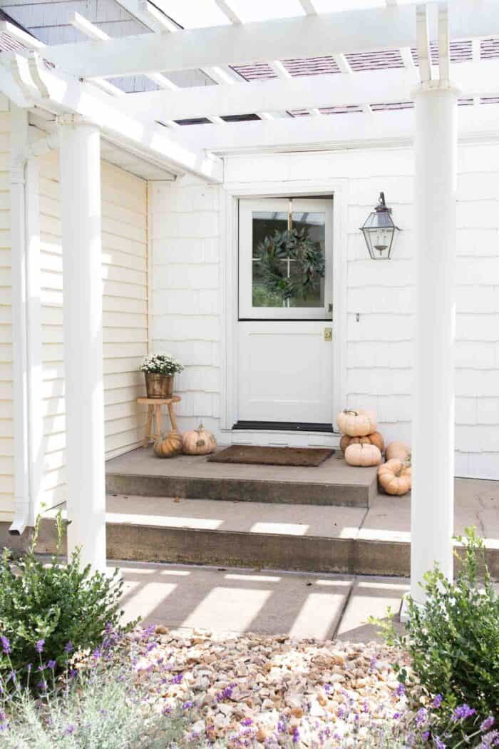 The concrete front porch of a white house with pumpkins for minimalist fall decor.