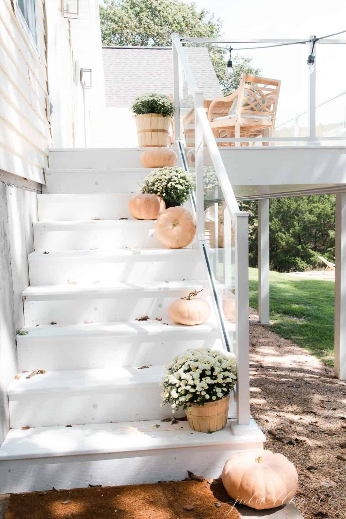 White deck steps decorated with minimalist fall decor, peach pumpkins and white mums.