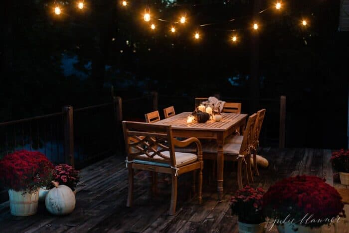 A deck dining area decorated for fall with string lights, pumpkins and mums