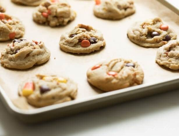 A gold sheet pan covered in fresh baked Halloween Monster Cookies.