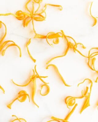 A marble surface with curls of dried orange zest to make dried orange powder.