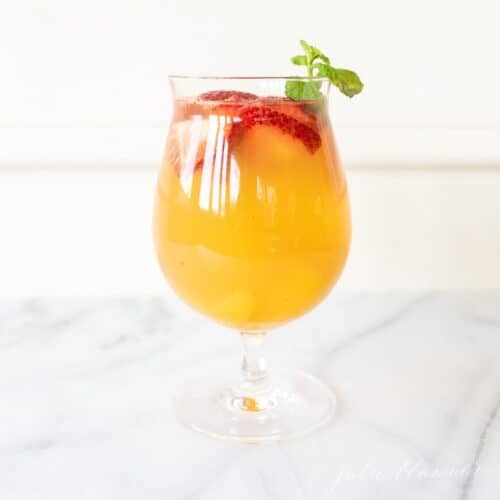peach sangria in a glass with strawberries and garnished with mint