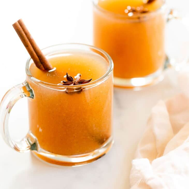 A pair of glass mugs full of pear cider, cinnamon sticks for garnish.