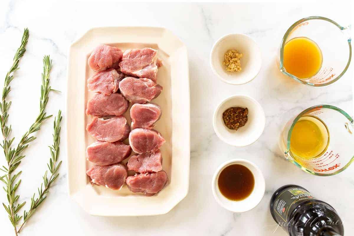 A marble surface with ingredients for a baked pork medallion recipe in an apple cider glaze.