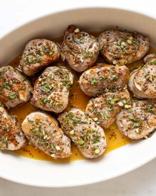 A white oval dish featuring cooked pork medallions in an apple cider glaze.