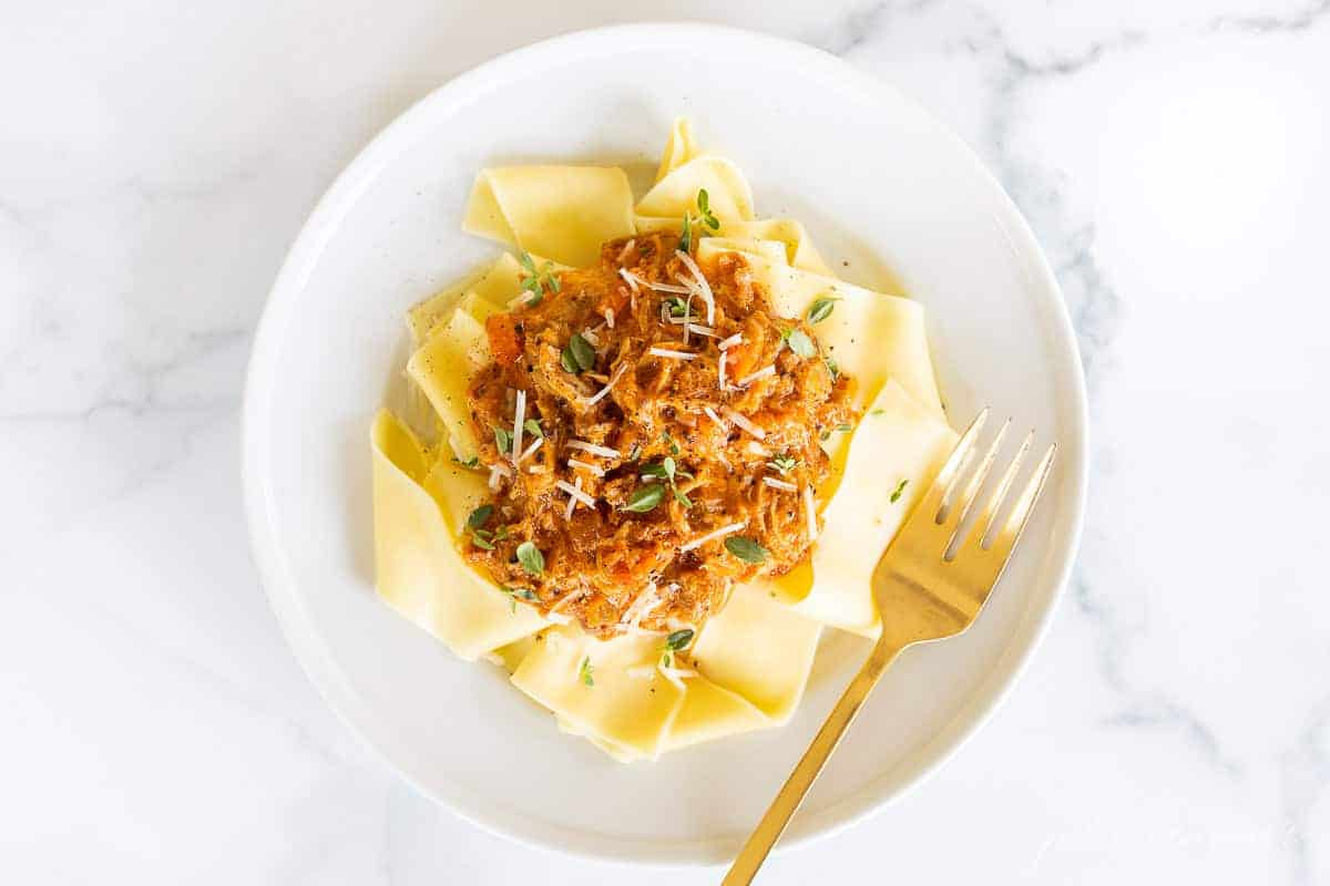 white plate of ragu on bed of pappardelle with gold fork