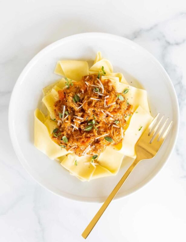 A white plate filled with pork ragu over pappardelle.