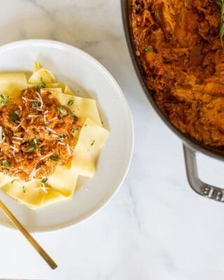 Pork ragu pasta on a plate with a cast iron pot full of pork ragu to the side.