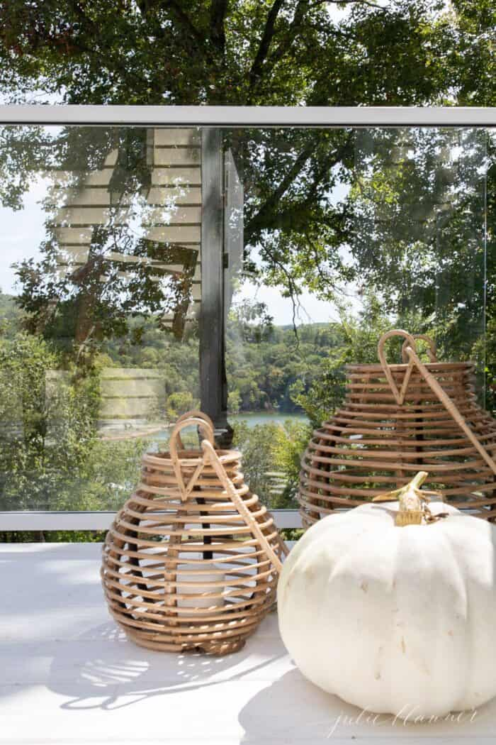 A white deck with glass railings and minimalist fall decor in the form of two rattan lanterns and a white pumpkin.