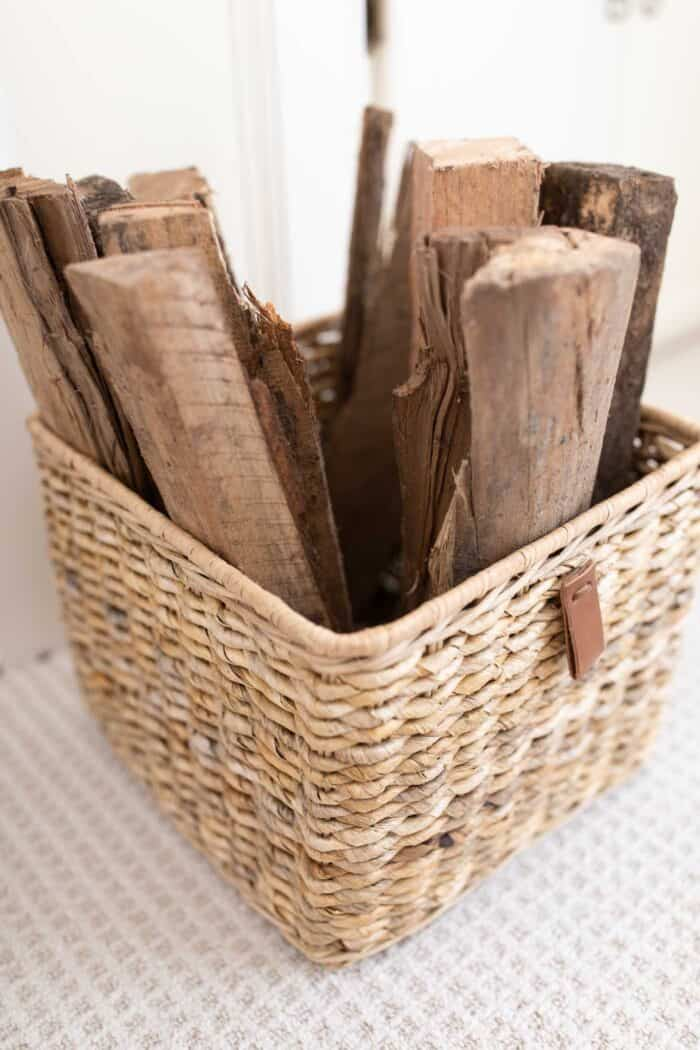 A textured basket filled with cut wood for a fireplace.