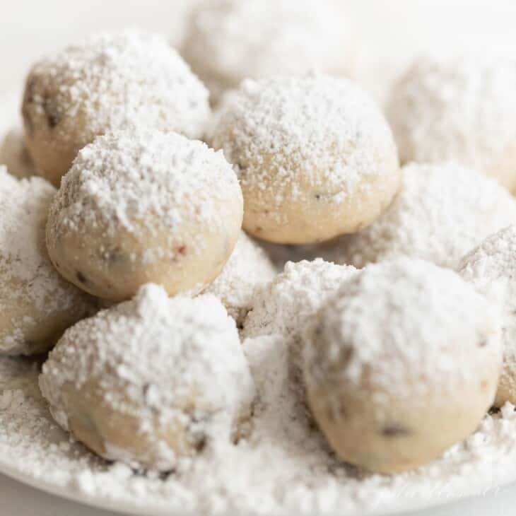 A plate of chocolate chip pecan snowball cookies, dusted in powdered sugar.
