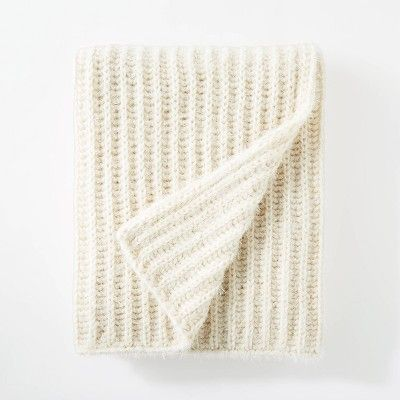 A chunky cable knit blanket in a cream color on a white surface.
