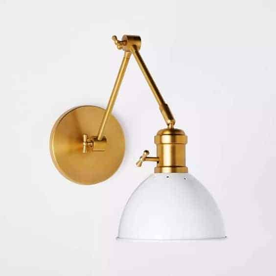 A gold sconce with a white shade.