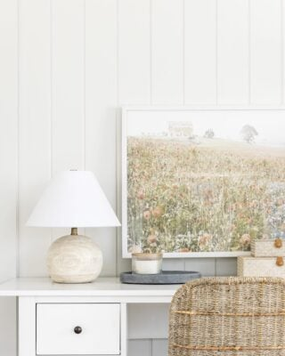 white desk with small lamp and art