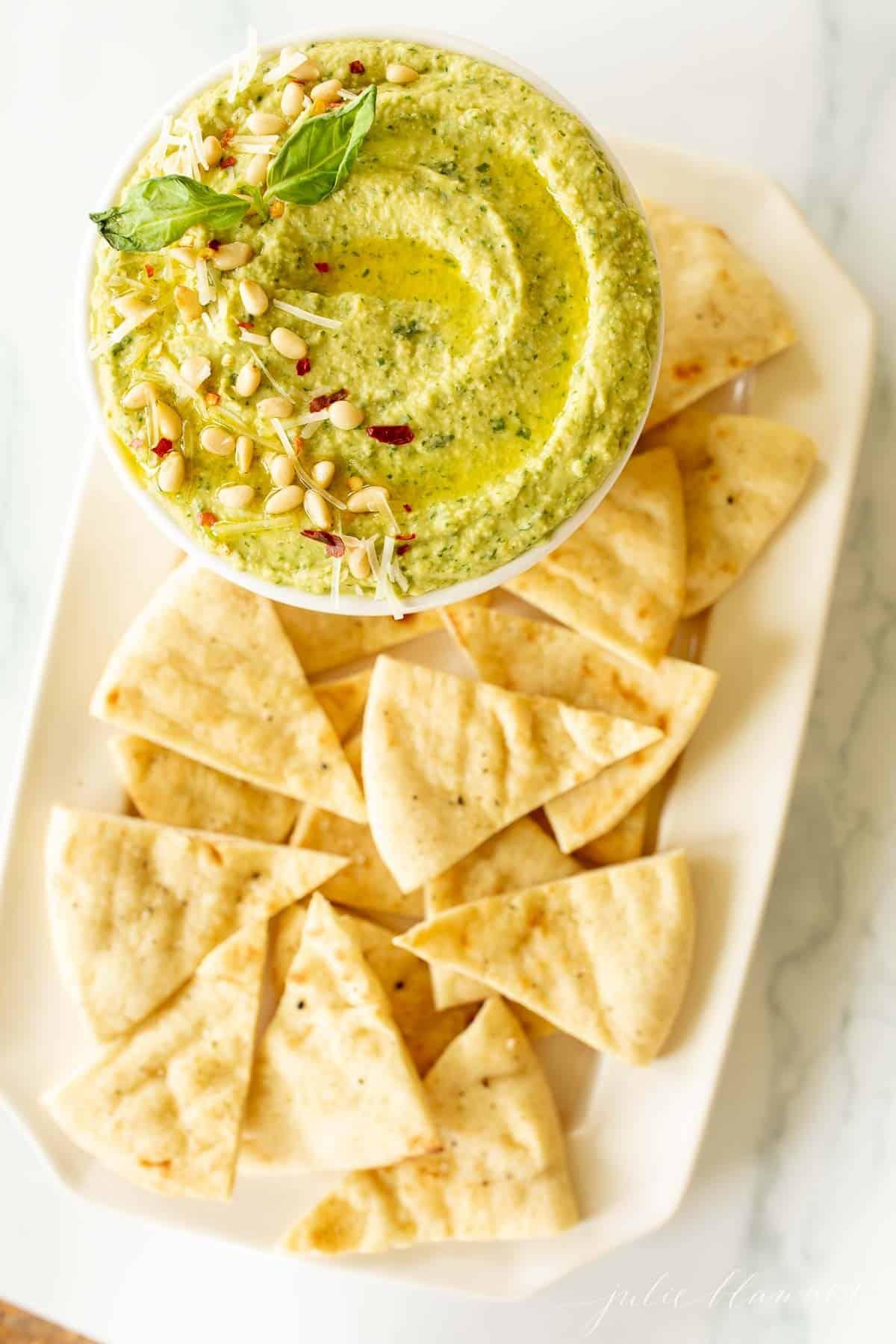 Un piatto di triangoli di pita con una ciotola di hummus al basilico.