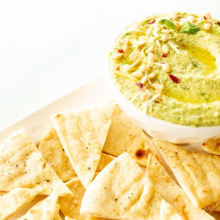 A platter full of pita triangles with a bowl full of basil pesto hummus.