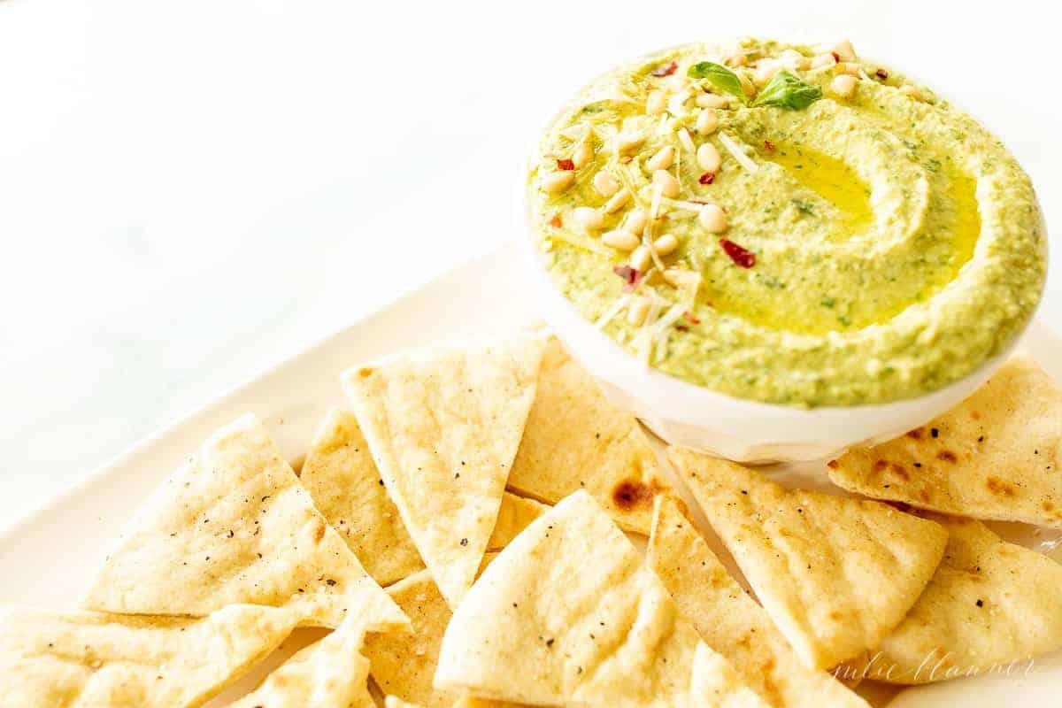 Un piatto di triangoli di pita con una ciotola di hummus al pesto di basilico.