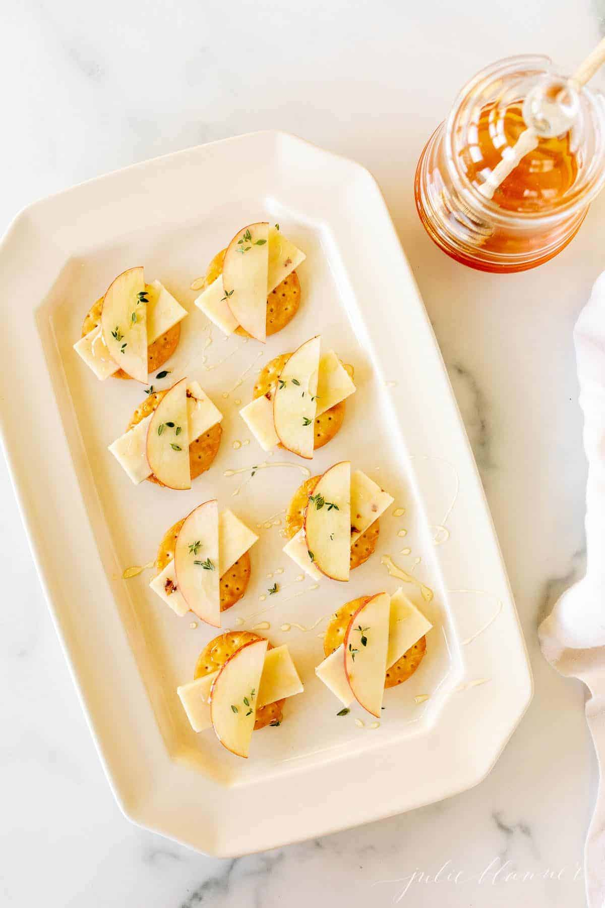 A rectangular white platter featuring a display of cheese and crackers.