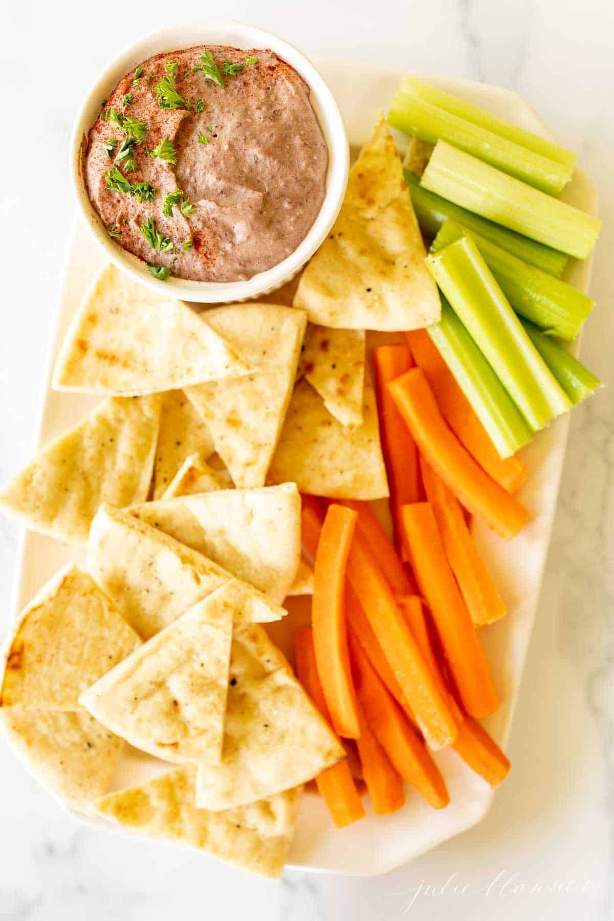 A white platter with a bowl of black bean hummus and pita triangles, celery and carrots.