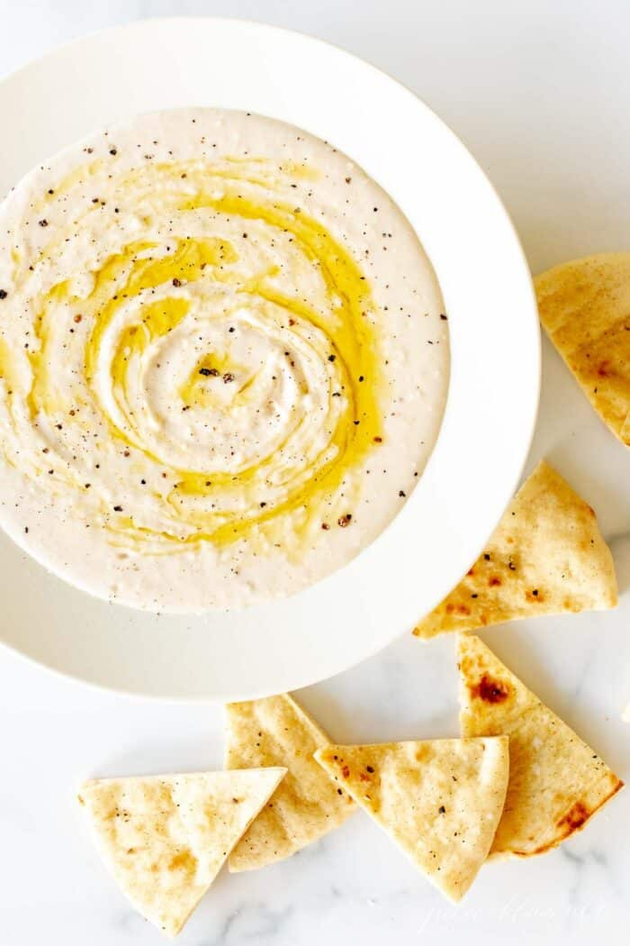 A white bowl filled with homemade white bean dip, drizzled with olive oil, pita triangles to the side.