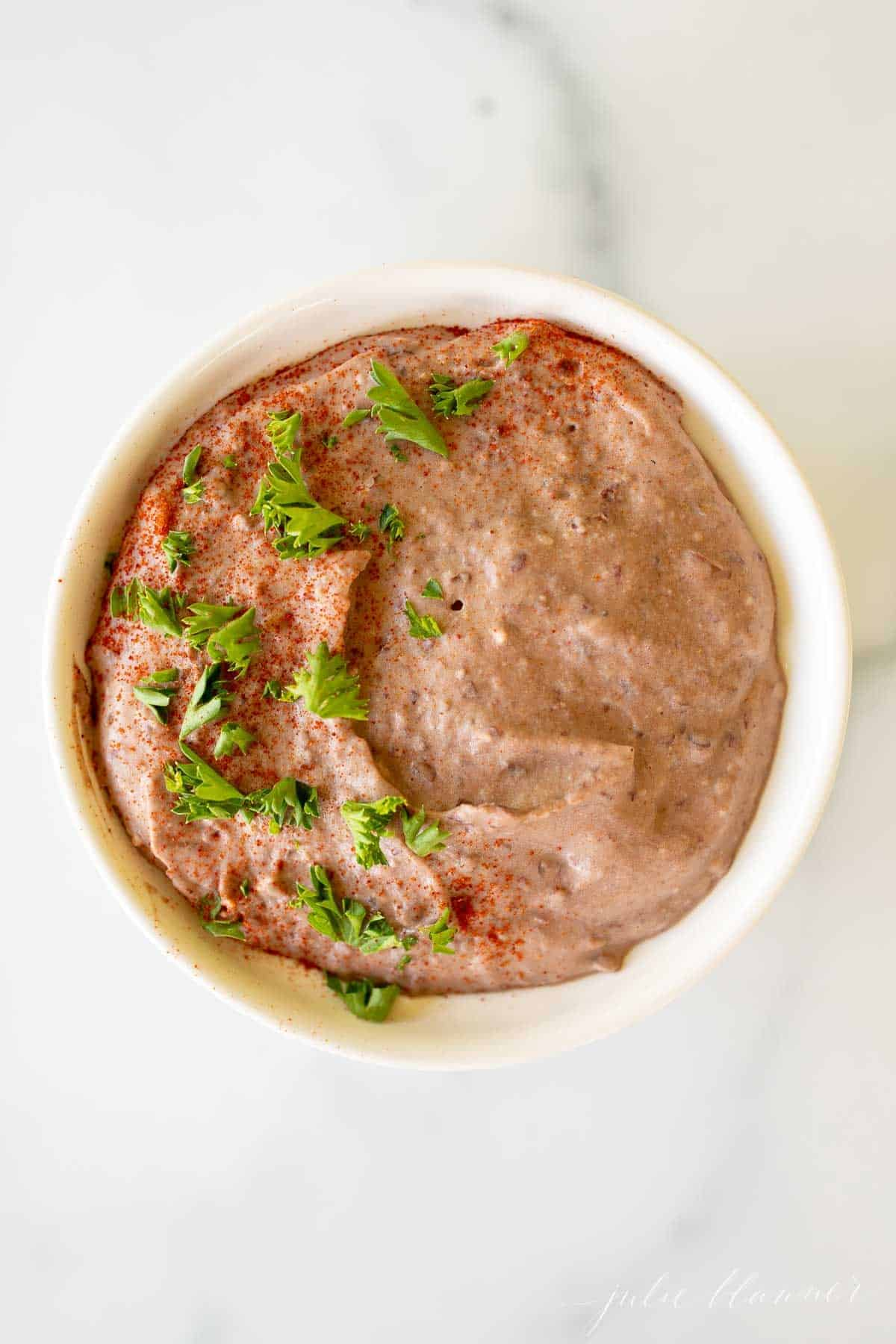 A white bowl full of black bean hummus topped with herbs