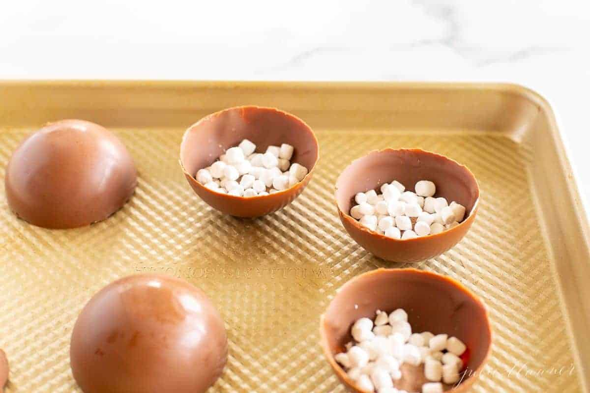 A gold baking sheet, with half spheres of hot chocolate bombs filled with hot cocoa mix and mini marshmallows.